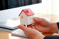 パソコンの前で家の模型を持つ男性の手