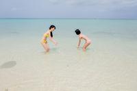 ビーチ 水着姿で記念撮影をする2人の女性観光客