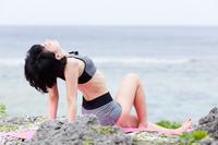 ビーチでヨガをする若い女性