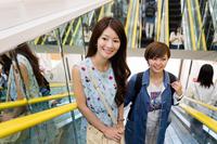 エスカレーターに乗る女性買い物客