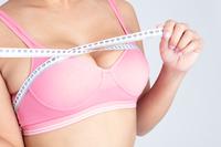 メジャーで体を測る女性