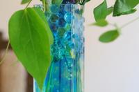 部屋のガラスの花瓶の青色のジェリーボールと緑の葉