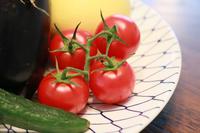 テーブルの上の皿に置かれたトマトや野菜