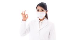 OKをするマスクをした白衣の若い女性
