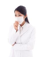 考えるマスクをした白衣の若い女性