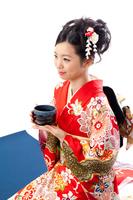 お茶を飲む着物の若い女性