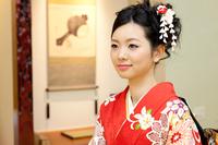 和室で座る着物の若い女性