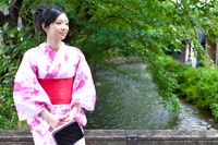 川辺にたたずむ着物の若い女性