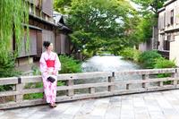 橋にたたずむ着物の若い女性