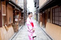 小路に立つ着物の若い女性