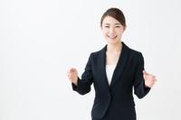 両手を前に出すスーツ姿の若い女性