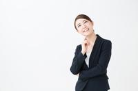 あごに手を当て考えるスーツ姿の若い女性