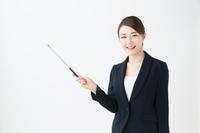 指示棒を持ったスーツ姿の若い女性