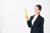 大きな鉛筆を持ったスーツ姿の若い女性
