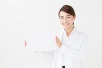 メッセージボードを持った白衣の若い女性