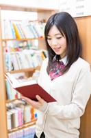 図書室で立ち読みをする女子学生