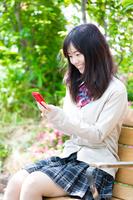スマートフォンを見る女子学生