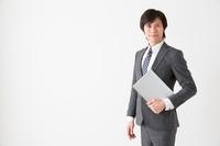 資料を小脇に持って笑顔なビジネススーツ姿の大人の男性一人