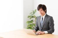観葉植物の隣でパソコン操作中に微笑むビジネススーツ姿の大人の男性一人