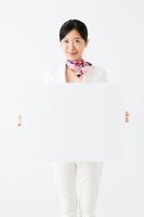 メッセージボードを持つ白いスーツ姿の女性