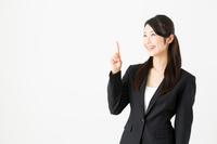 黒いスーツ姿で右手人差し指を立てる若いビジネスウーマン