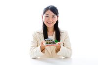 住宅模型を説明する若い女性