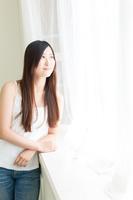 カーテン越しに外を覗く髪の長い若い女性
