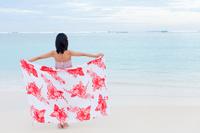 海に向かってパレオを広げる髪飾りのマキシワンピースの若い女性