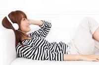 ソファーに横になって音楽を聴くTシャツの若い女性