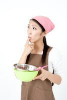 味見をしながらお菓子づくりをする女性