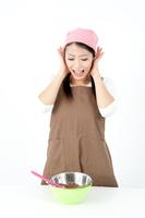 頭に手をあてお菓子づくりをする女性