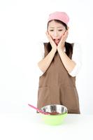 頬に手をあてお菓子づくりをする女性