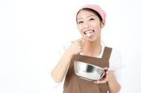 味見をしながら料理をする女性