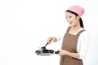 フライパンとターナーを持ち料理をする女性