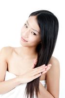 手で髪を触るロングヘアーの女性