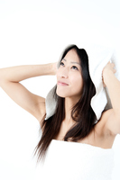 タオルで髪を乾かすロングヘアーの女性
