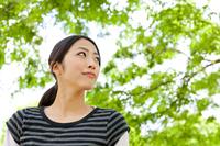 木陰に立つカジュアルウェアの若い女性