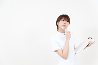 メモをとる白衣姿の若い女性