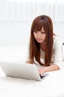 ノートパソコンを操作する長い髪の女性