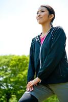 公園でストレッチをする若い女性