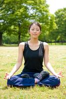 公園の芝生で瞑想する若い女性
