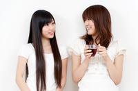 カップを持ち談笑する2人の若い女性