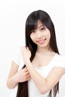 ロングヘアーを手で整えている若い女性