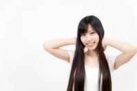 両手を頭の後ろに組むロングヘアーの若い女性