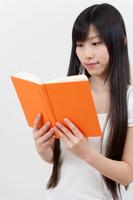 両手に本を持ち読書しているロングヘアーの若い女性