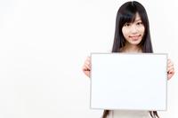 メッセージボードを持って立っている若い女性