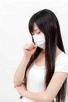 マスクをして咳をする若い女性