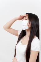 マスクをして額に手を当てる若い女性