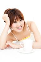 ソフトドリンクを飲むキャミソール姿の若い女性