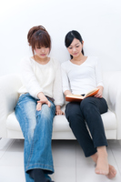 ソファーに座って同じ本を見る二人の若い女性